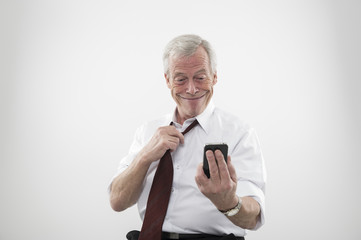 Senior man smiling at a mobile phone