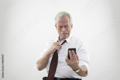Senior man reacting in disgust to his mobile
