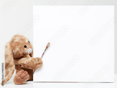 Stuffed bunny peeking behind blank board