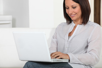 Woman sitting on couch with computer