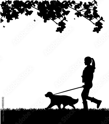 Girl walking a dog in park in spring silhouette