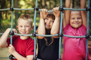 Happy children holding a net on playground