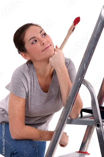 Woman with paint brush leaning on ladder