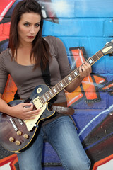 Female guitarist stood by painted wall