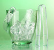 Glass ice bucket on light green background