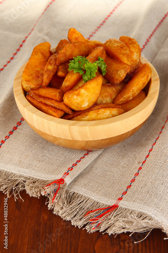 Appetizing village potatoes in bowl on wooden table close-up