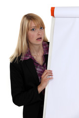 Shocked blond woman stood by blank flip chart