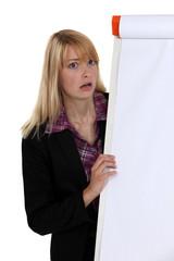 Shocked blond woman stood by blank flip chart