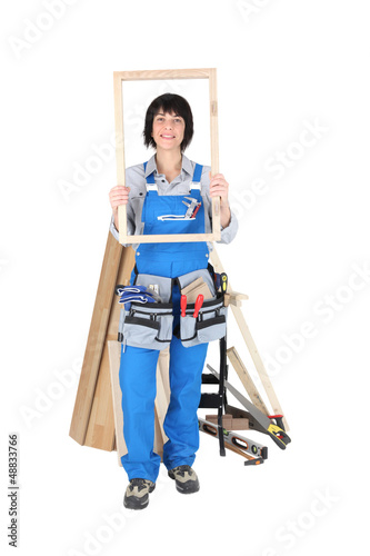 Female carpenter with a wooden frame