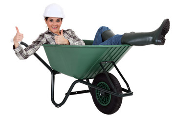 female bricklayer thumbs up in wheelbarrow