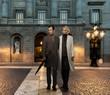 Elegant couple in coats against building facade in evening