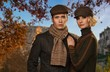 Elegant couple in caps against autumnal landscape