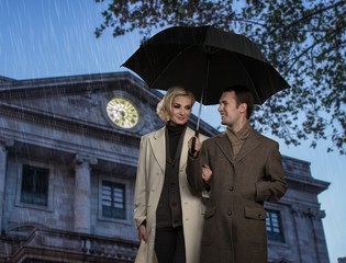 Elegant couple with umbrella against building facade