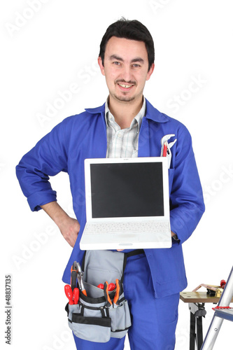 30 years old artisan showing a laptop in a room full of tools