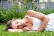 Junge Frau im Sommerkleid im Garten ausruhend
