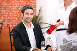 Waitress bringing wine to customer