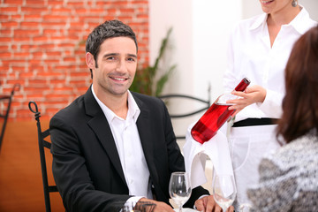 Waitress bringing wine to customer