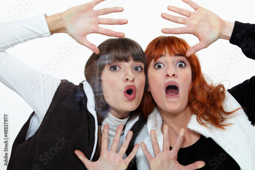 Two friends pressing their face on a pane.