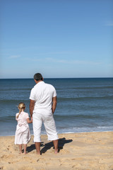 A father and his daughter looking at the sea.