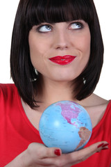 Woman in red holding planet earth