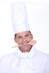 male cook with a wooden spoon in the mouth