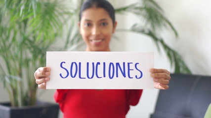 Young woman holding a solutions sign.
