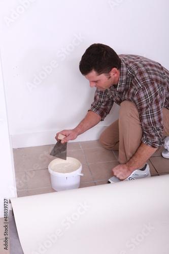 Man sticking carpet