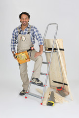 Carpenter with a stepladder and wooden shutter
