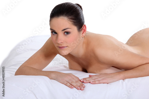 Portrait of a nude woman lying on a mattress