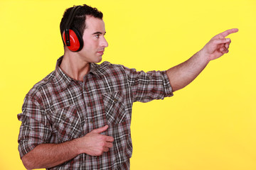 laborer with headphones on yellow background