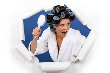 Angry woman with hair rollers and brush