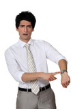 Businessman angrily pointing to his watch