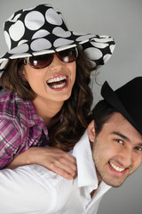 Couple messing around in hats