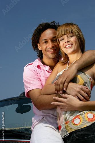 Smiling couple embraced in front of a car