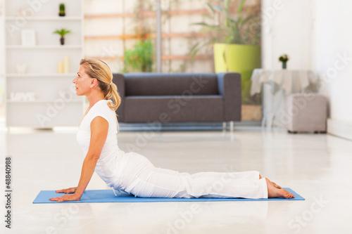 elegant mature lady doing yoga at home
