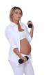 Pregnant woman using handweights