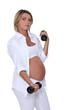 Pregnant woman using handweights