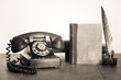 Vintage phone, old book, quill and inkwell on wooden table