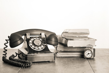 Retro telephone, old clock, books on table sepia photo