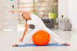 fit middle aged woman workout on exercise ball