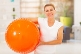 fit mature woman holding exercise ball at home
