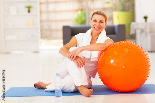 happy senior woman resting on mat after exercise at home