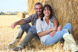 Couple sitting in front of haystack
