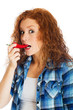 redhead woman taking bite of spicy red pepper