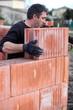 Mason placing brick on unfinished wall