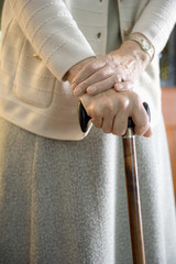Caucasian older woman walking with cane