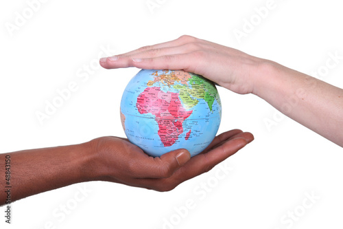 Two hands touching miniature globe
