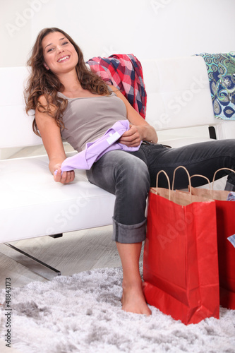 Exhausted brunette sat on couch with her purchases