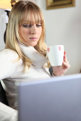 cute young blonde having coffee while working on laptop