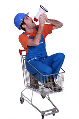 Tradesman sitting in a shopping cart